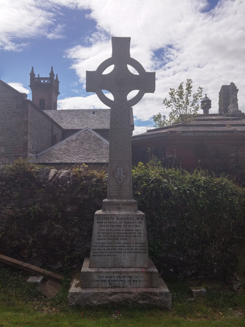 A Celtic cross gravestone to Elizabeth Blackwell with a church in the background