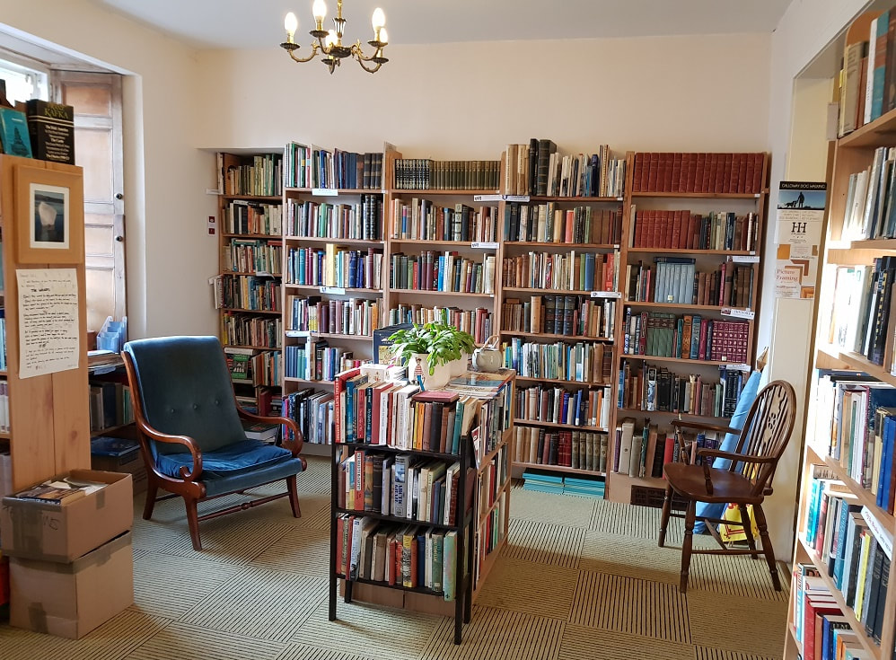 A room with rows of shelves filled with books and two armchairs