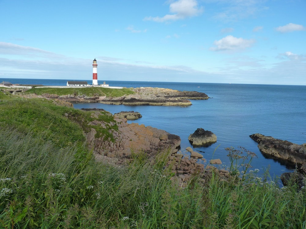 A red and white striped lighthouse sitting an a rocky outcrop