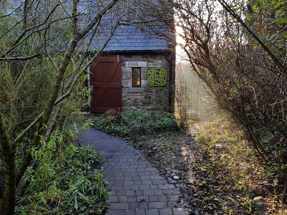 A pathway leading to a stone building with a sign reading 'Byre Books'