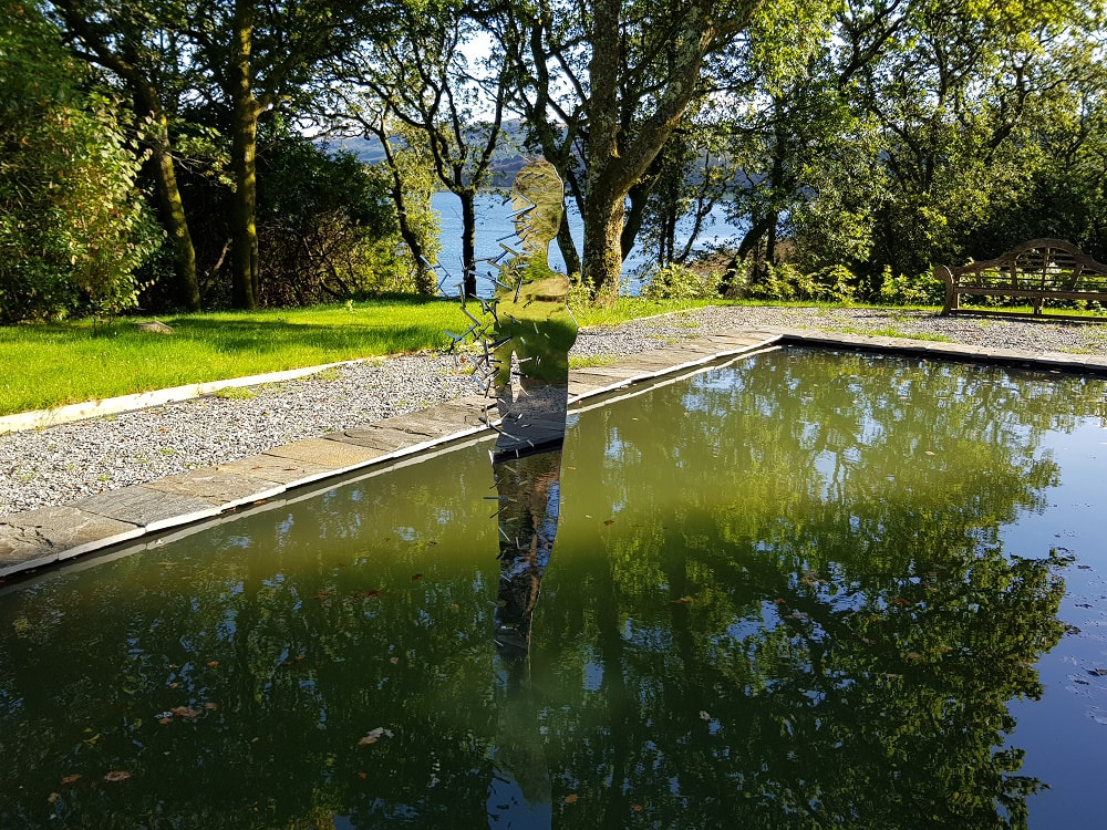 A mirrored sculpture of a female figure standing in a pool of water