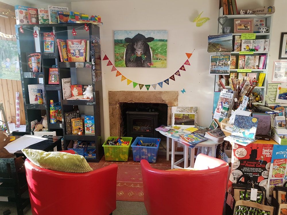 The interior of a bookshop with shelves of children's books and two small red chairs
