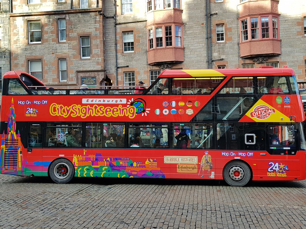 A red open top bus with the words Hop on Hop Off Edinburgh CitySightseeing on the side