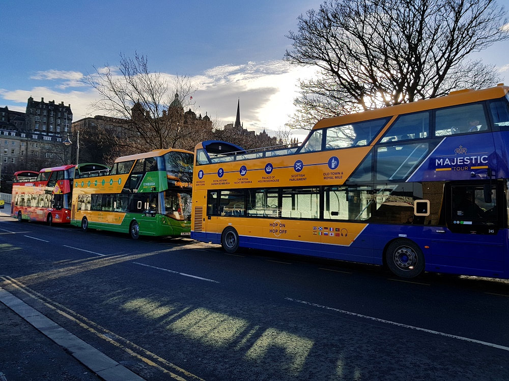 Three open top tour buses stopped at a bus stop