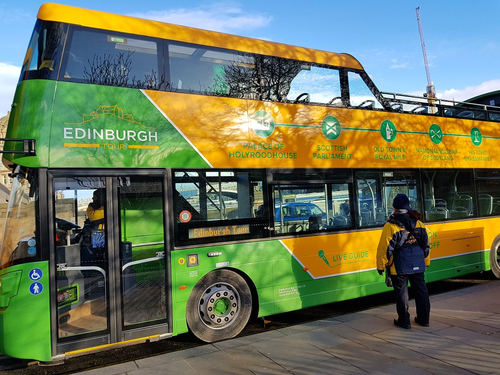 A green and yellow open top bus with the words Edinburgh Tour