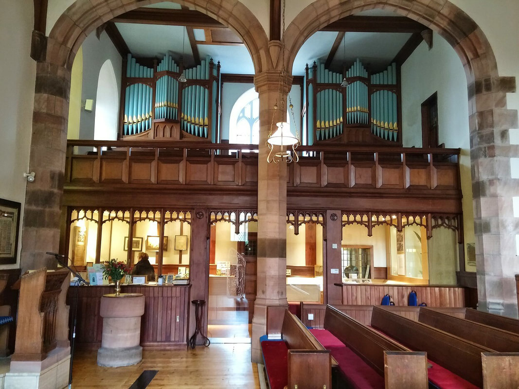 The interior of a church with pews in the foreground and an organ on the far wall
