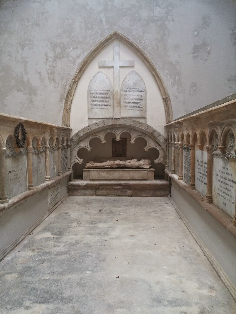 A white marble mausoleum with a carved effigy in the background and memorial stones on either side