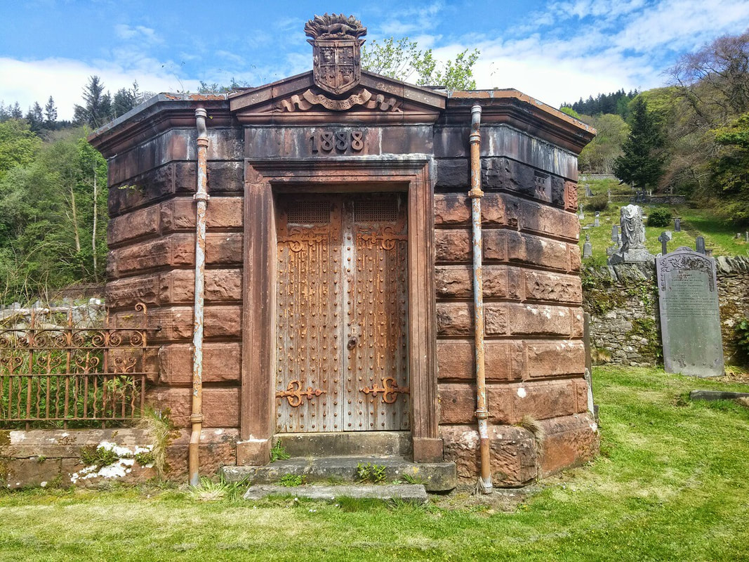 A brown stone vault with an oak door and the Douglas family coat of arms