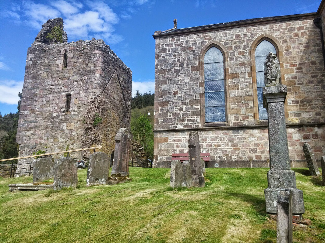 Graveyard with corner of church showing and a ruined stone tower