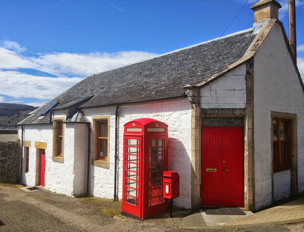 A white cottage with a red door and a red telephone box and post box outside