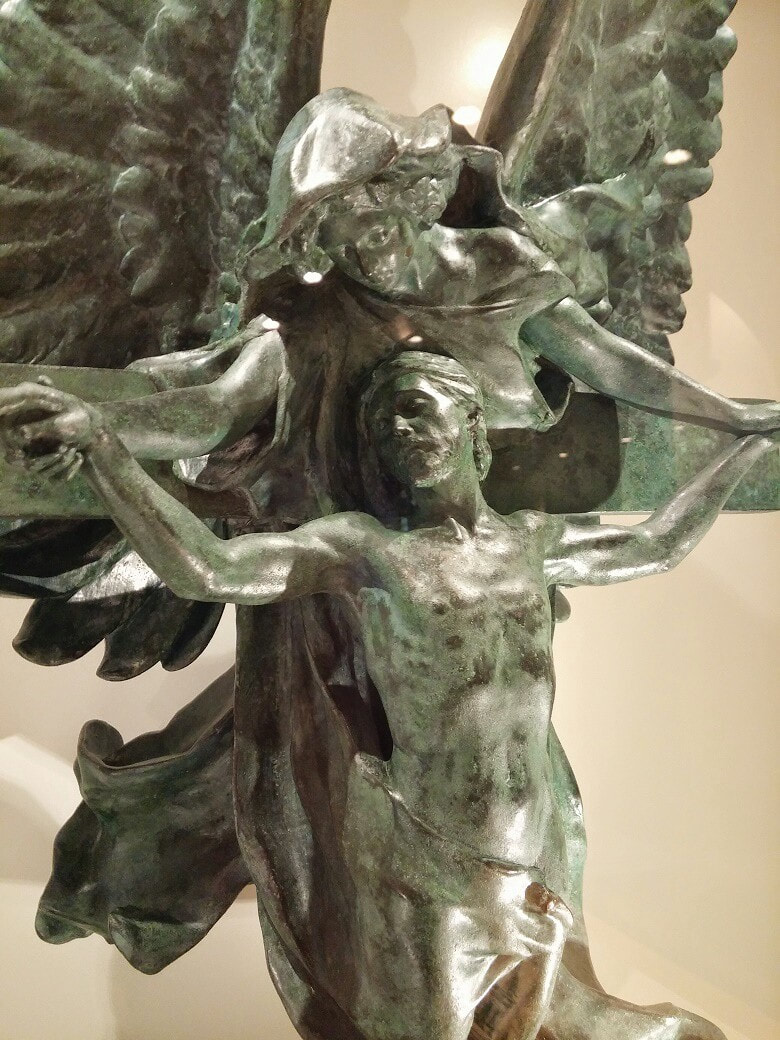 A sculpture of Jesus on the cross with an angel holding his hands