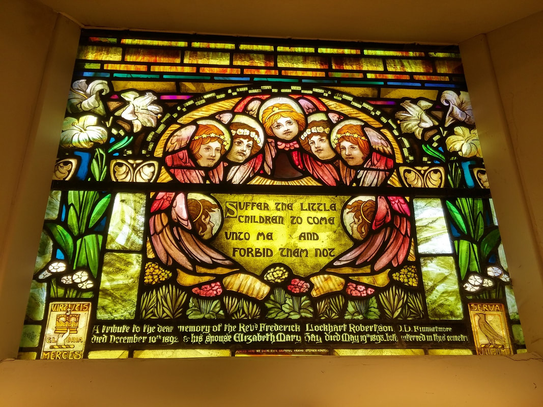 Stained glass window with seven angels in the centre surrounded by flowers