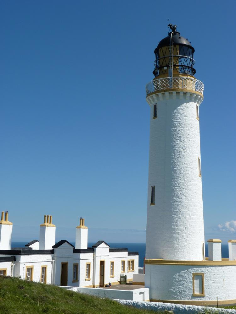 A white washed lighthouse overlooking the sea.