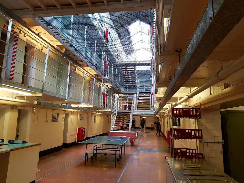 The inside of a prison building with three storeys of cells.  A table tennis set sits on the ground floor and several people are walking around