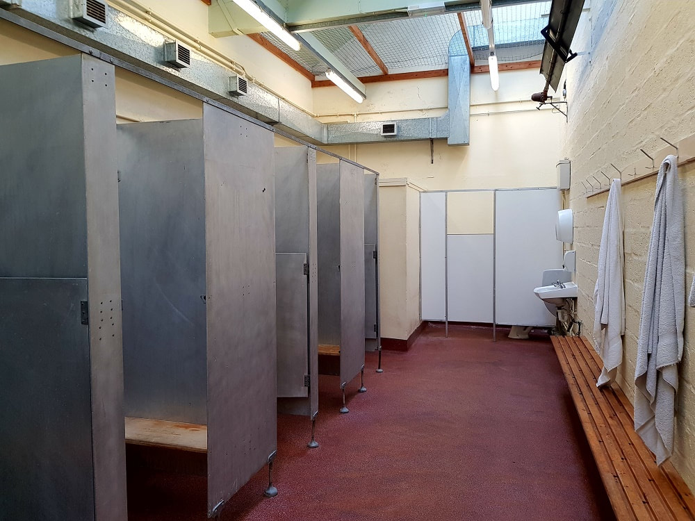 Four metal shower cubicles on one side and white towels hanging on pegs on the opposite wall