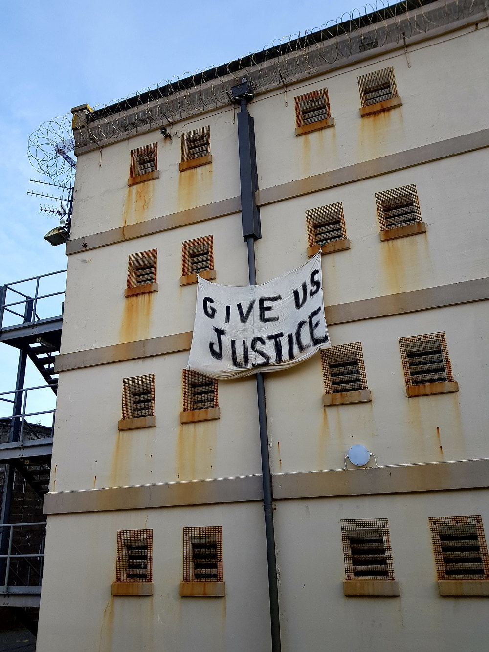 A beige building with a white banner hanging from one window reading ' Give us justice'