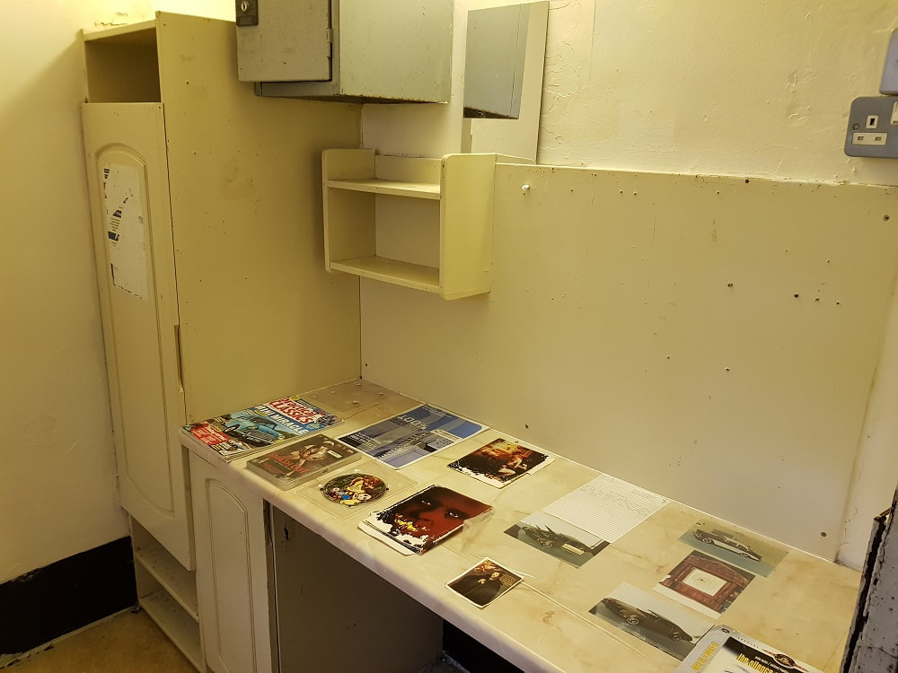 The interior of a prison cell with a cupboard, shelving and a desk with magazines on top