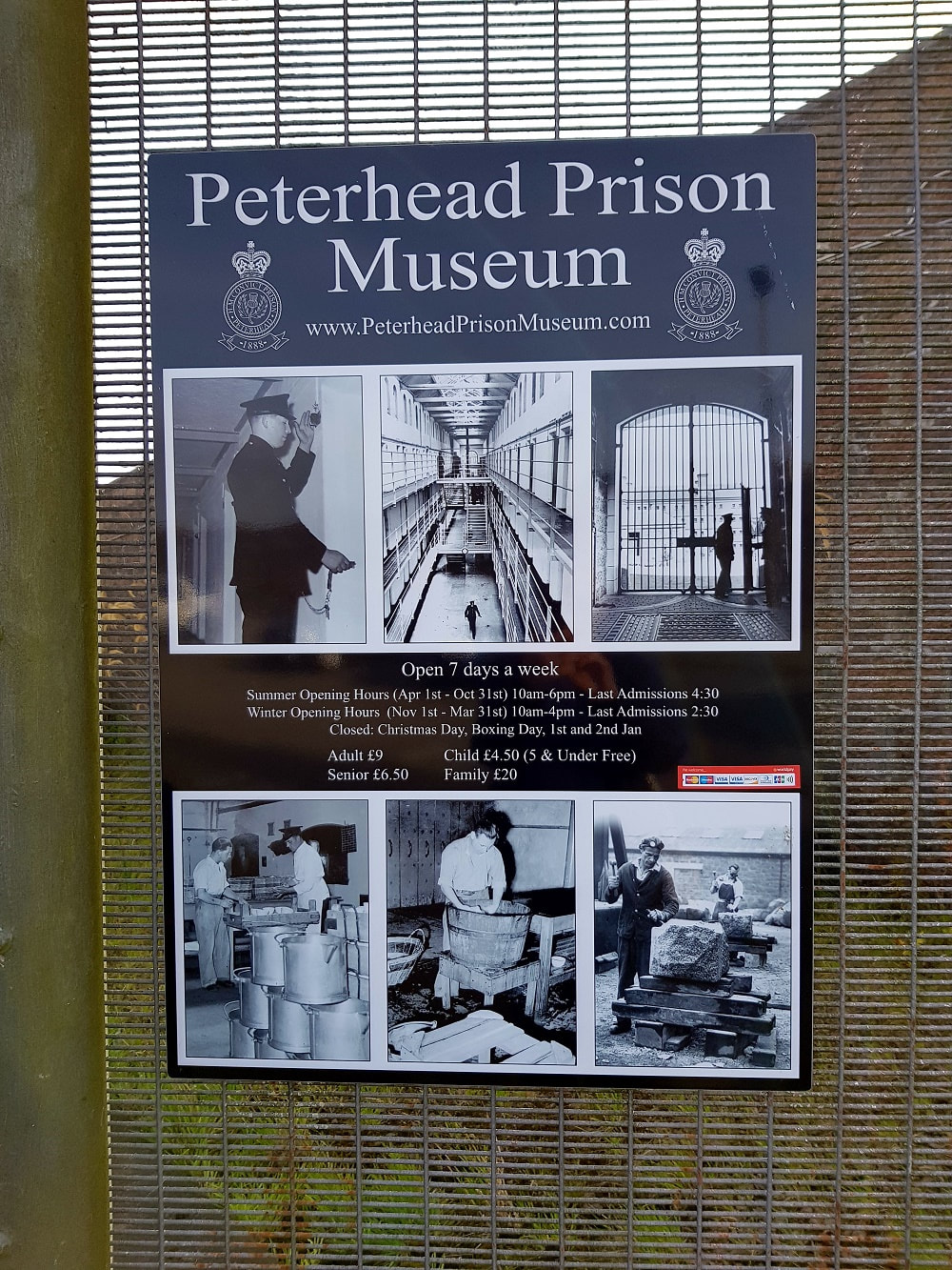 A black and white sign attached to a gate with details of Peterhead Prison Museum opening times and entry costs