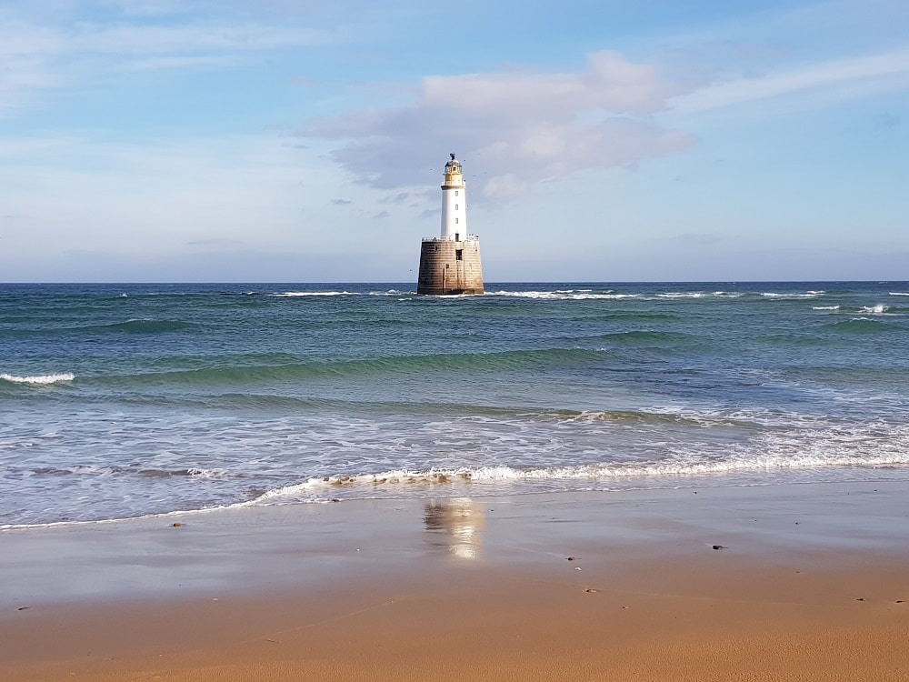 A white lighthouse surrounded by water