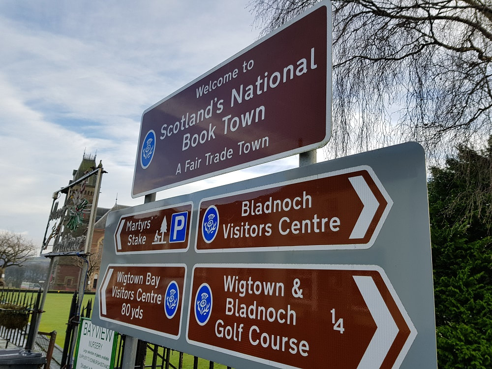 Brown sign reading Scotland's National Book Town, A Fair Trade Town