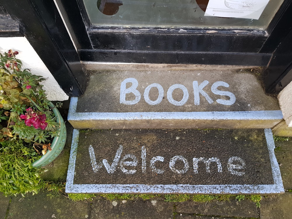 Two stone steps with the words 'Books' and 'Welcome' written on them