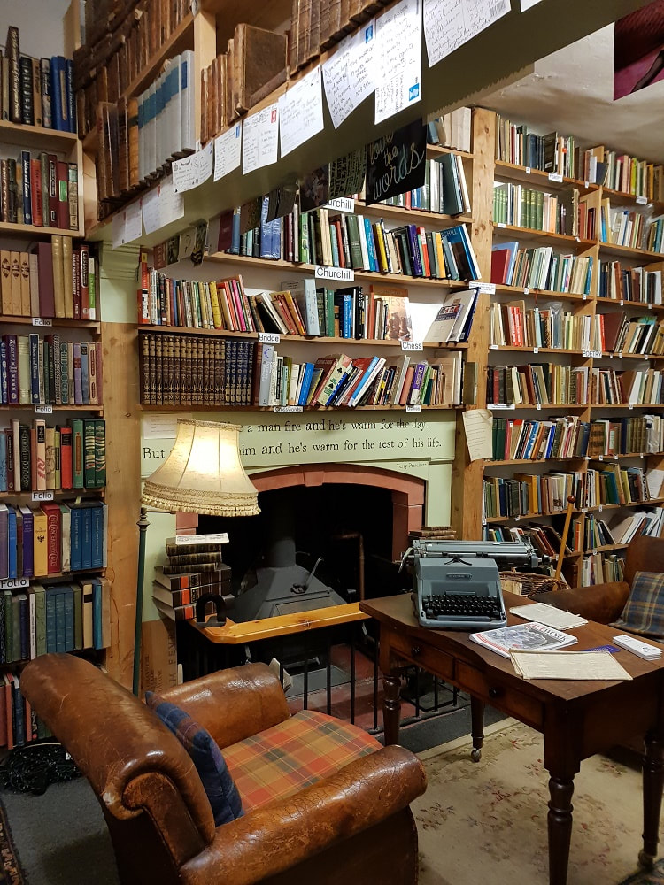 A room with rows of shelves filled with books, a leather armchair and a wooden table with a typewriter on top