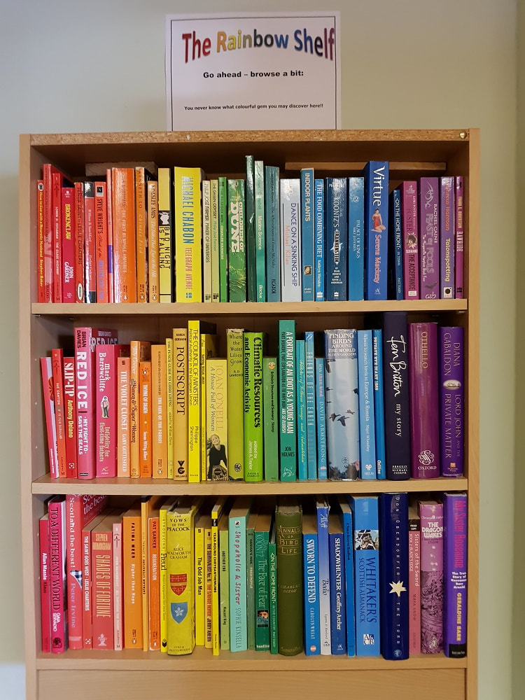 Three rows of shelves filled with multi-coloured books and a sign reading 'The Rainbow Shelf, Go ahead-browse a bit'
