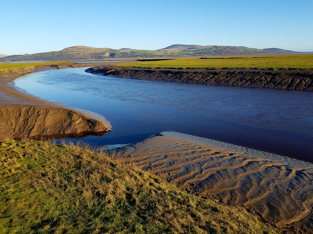 A river flowing through a silted estuary with green hills in the background