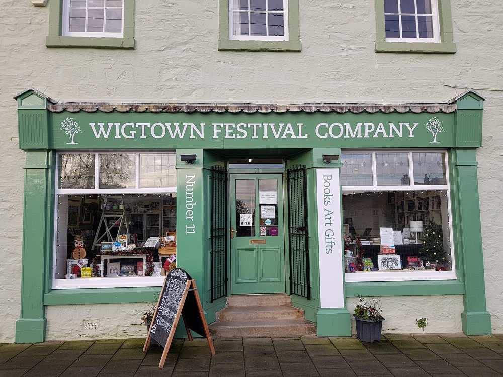 A green shop front with the sign 'Wigtown Festival Company'